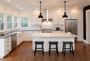 Bright and beautiful new, modern kitchen in luxury home with low hanging lights above a white kitchen island