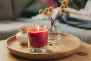 Scented candle burning on sofa table ona  wooden tray next to some fragrance sticks