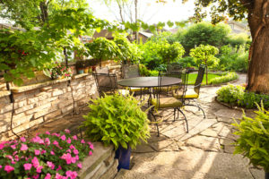 Landscpaed back graden with shrubs, trees and flowers, along with outdoor seating and table on a summer day