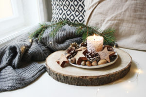 Winter festive still life scene. Burning candle decorated by wooden stars, hazelnuts and pine cones standing near window on wooden cut board.