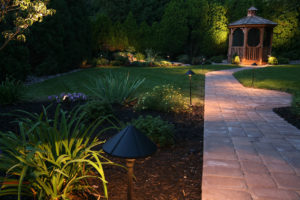 dark winter evening in a well lit garden, with a path leading down to a gazebo