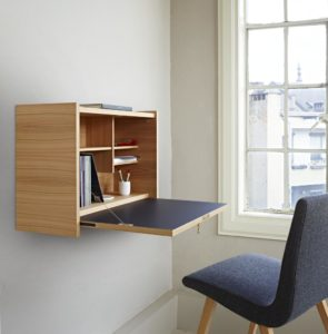 small fold down desk in city apartment next to window