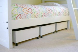 rolling boxes stored underneath a child's bed