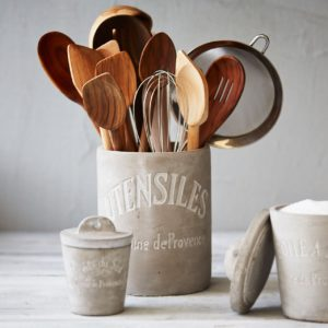 spatulas and other kitchen utensils stored ina utensil holder in a white kitchen