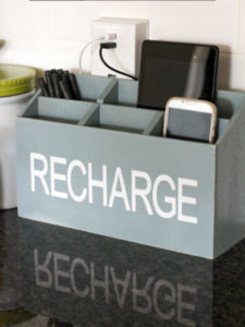 old magazine rack reused as a charging station for phones and laptops