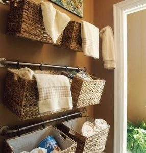 towels stored in hanging baskets in a clean and organised bathroom
