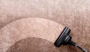 a vacuum cleaner cleaning a brown carpet in a home