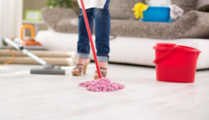 woman mopping a dirty floor in her house