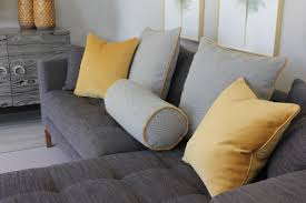 yellow and grey cushions on a grey sofa in a living room